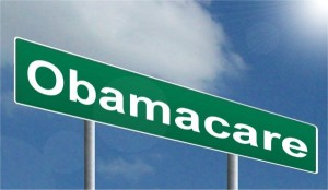 Road sign with the words Obamacare written in white on a green background set against the sky.